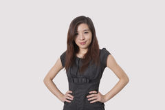 Portrait of beautiful young businesswoman with hands on hips over white background Stock Photos