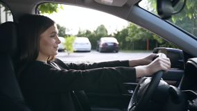Portrait of beautiful young businesswoman sitting on the driver`s seat,looking in the mirror and happily smiling stock video