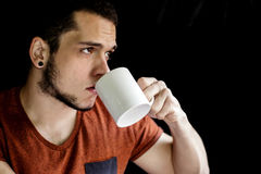 Portrait of a beautiful young caucasian man drinking from a white cup over plain black background Royalty Free Stock Photo