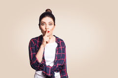 Portrait of beautiful young caucasian woman with black hair bun holding index finger at lips Stock Photography