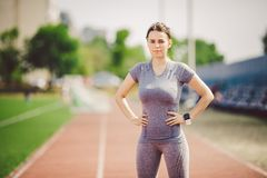 Portrait of a beautiful young caucasian woman with long hair in the tail and big breasts posing in gray sportswear standing traini. Ng on a running stadium, a stock images