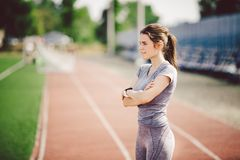 Portrait of a beautiful young caucasian woman with long hair in the tail and big breasts posing in gray sportswear standing traini. Ng on a running stadium, a royalty free stock photos