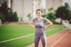 Portrait of a beautiful young caucasian woman with long hair in the tail and big breasts posing in gray sportswear standing traini. Ng on a running stadium, a stock photo