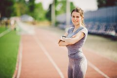 Portrait of a beautiful young caucasian woman with long hair in the tail and big breasts posing in gray sportswear standing traini stock image