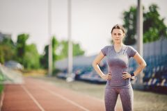 Portrait of a beautiful young caucasian woman with long hair in the tail and big breasts posing in gray sportswear standing traini. Ng on a running stadium, a stock photography