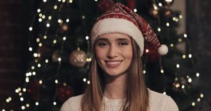 Portrait of Beautiful Young Caucasian Women Wearing Santas Hat Standing near the Christmas Tree at Cosy Christmas stock video footage