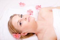 Portrait of beautiful young charming, attractive blond woman relaxing lying during spa procedures surrounded with flowers Royalty Free Stock Image