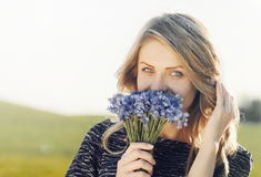 Portrait of a beautiful young cheerful woman with cornflowers Stock Image
