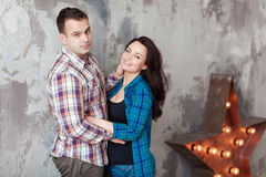 Portrait of beautiful young couple in casual clothes hugging and smiling, standing against gray wall Stock Photo