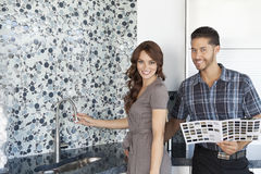Portrait of beautiful young couple with color samples standing in model home kitchen Royalty Free Stock Image