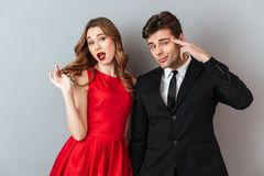 Portrait of a beautiful young couple dressed in formal wear. Posing while holding hands and looking at camera over gray wall background Stock Image