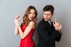 Portrait of a beautiful young couple dressed in formal wear. Standing back to back and showing gun gesture over gray wall background Stock Photo