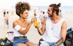 Beautiful young couple drinking orange juice in the street. Royalty Free Stock Photos