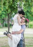 Portrait of beautiful young couple female bride and male bridegroom hugging in summer park. Man husband raised woman wife and look. Portrait of beautiful young Royalty Free Stock Image