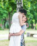 Portrait of beautiful young couple female bride and male bridegroom kissing in summer park. Man husband holding woman wife in his Royalty Free Stock Photo