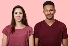 Portrait of beautiful young couple looking smiling at camera, on pink wall background, wears casual t shirts, have cheerful facial royalty free stock photography