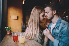 Portrait of beautiful young couple in love at a coffee shop. Royalty Free Stock Images