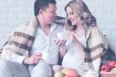 Portrait of a beautiful young couple, pregnant girl having breakfast at home having covered plaid stock image