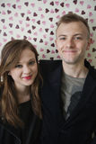Portrait of beautiful young couple smiling over heart shaped wallpaper Stock Image