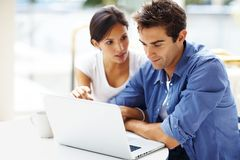 Portrait of beautiful young couple using laptop Stock Photography