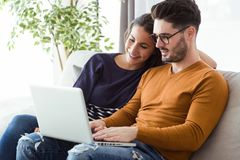 Beautiful young couple using laptop on the sofa at home. Stock Image