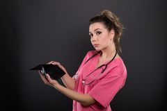 Portrait of beautiful young doctor showing empty wallet Stock Images
