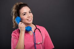 Portrait of beautiful young doctor talking at telephone receiver. On black background with copypsace advertising area Stock Photography