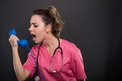 Portrait of beautiful young doctor yelling at telephone receiver royalty free stock photos