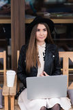 Portrait of a beautiful a young dreamy woman with nice look thinking about something during work on net-book Stock Photography