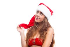 Portrait of a young girl in a santa hat, smiling and dreamily looking up. Isolated on white. Portrait of a beautiful young European brunette girl dressed in a Stock Photos