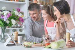 Portrait of beautiful young family cooking together at kitchen. Young family cooking together at kitchen at home royalty free stock image