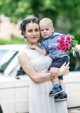 Portrait of a beautiful young female bride holding small baby boy with wedding roses bouquet and looking into camera at sunny summ. Er park. Mother and her Royalty Free Stock Photo