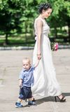 Portrait of a beautiful young female bride walking with small baby boy to wedding ceremony. Mother and her little son on her weddi. Ng at sunny day at summer Stock Photos