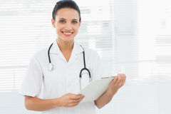 Portrait of a beautiful young female doctor with clipboard Royalty Free Stock Image