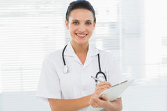 Portrait of a beautiful young female doctor with clipboard Stock Photography