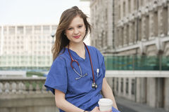 Portrait of a beautiful young female doctor having a coffee break Stock Photography