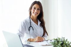 Beautiful young female doctor looking at camera in the office. stock photo