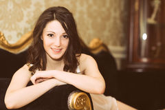 Portrait of beautiful young female on luxury sofa. Royalty Free Stock Photography