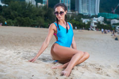 Portrait of beautiful young female model in swimwear sitting on the beach at tropical resort.  Stock Photo