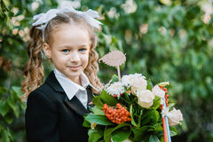 Portrait of a beautiful young first-grader with red apple on books in a festive school uniform Royalty Free Stock Photography