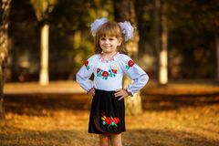 Portrait of beautiful young first-grader in festive school uniform on background autumn park. Beginning of lessons royalty free stock photo