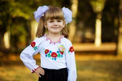 Portrait of beautiful young first-grader in festive school uniform on background autumn park. Beginning of lessons stock images
