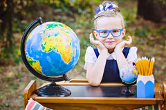 Portrait of a beautiful young first-grader sitting at a desk Stock Image