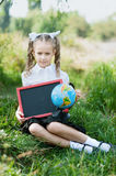 Portrait of a beautiful young first-grader with red apple on books in a festive school uniform Stock Photo