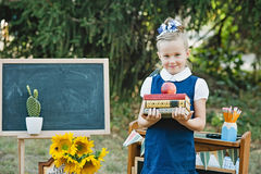 Portrait of a beautiful young first-grader standing with books Stock Images