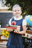 Portrait of a beautiful young first-grader standing with books Royalty Free Stock Photo