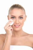 Portrait of beautiful young girl applying on face cosmetic pad. Stock Photos