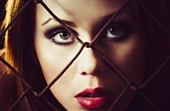 Portrait of beautiful young girl behind the metallic grid. Closeup Stock Photos