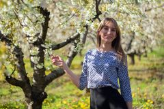 Portrait of beautiful young woman in apple trees blooming park on a sunny day. Smiling girl Happy girl. Happiness royalty free stock photography