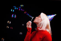 Portrait of a beautiful young girl blowing bubbles. Attractive happy blonde blowing bubbles at party Stock Photography